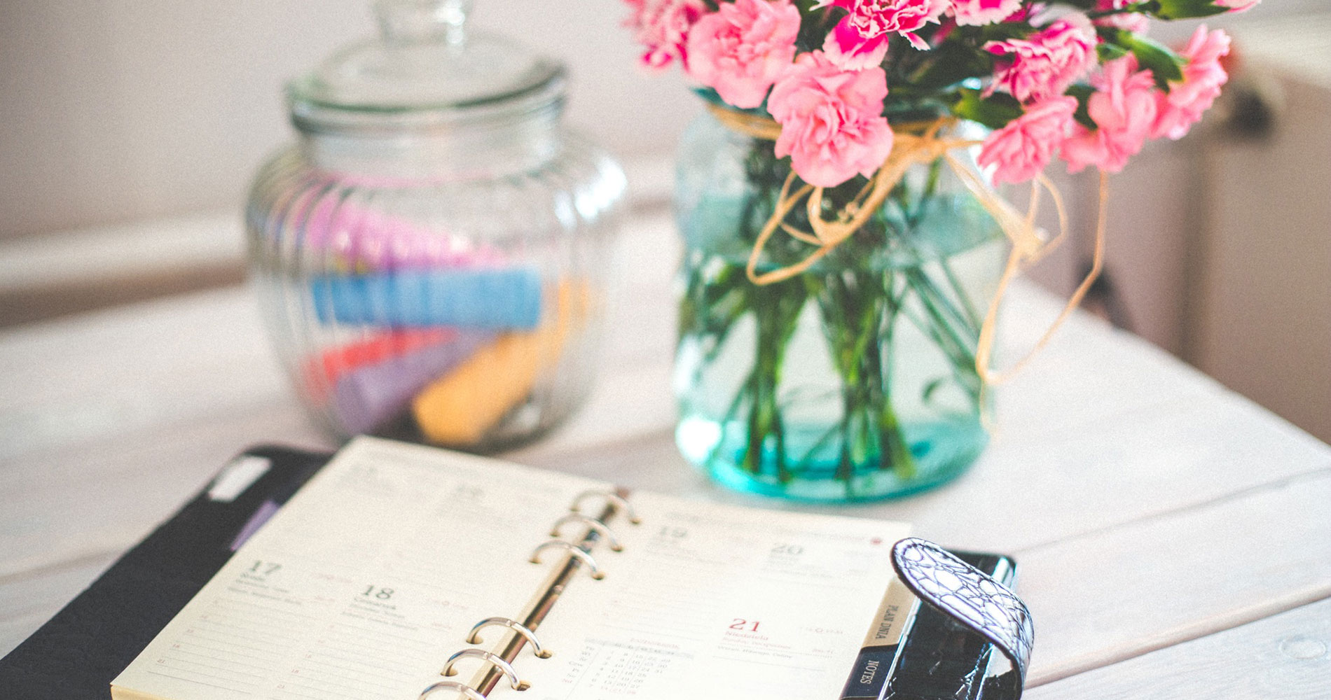 Planner and flowers on vintage desk