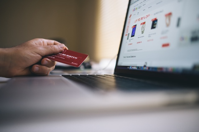 Man shopping online with credit card in hand