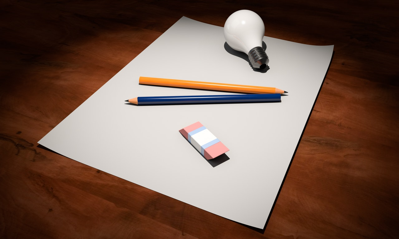 Paper pencils eraser lightbulb on desk